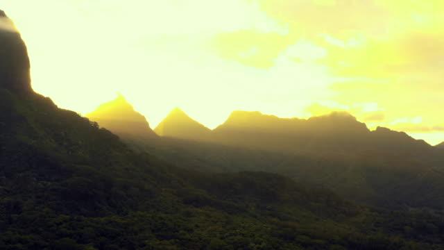 vidéos et rushes de aerial: sun shines through moorea's mountains as it rises, moorea, french polynesia - moorea