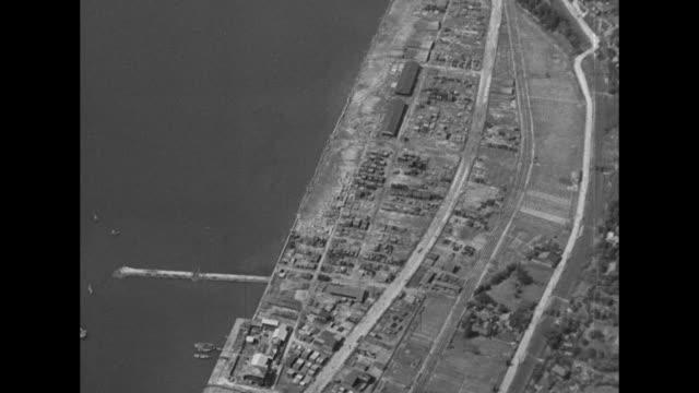 sunken battleship off shore of town nestled in hills / VS Yokosuka Naval Base not a lot of damage to buildings or ships / island in Kure Harbor lots...