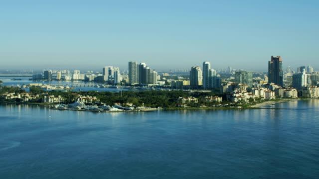 vidéos et rushes de aerial sunrise fisher island luxury condominiums florida usa - biscayne bay