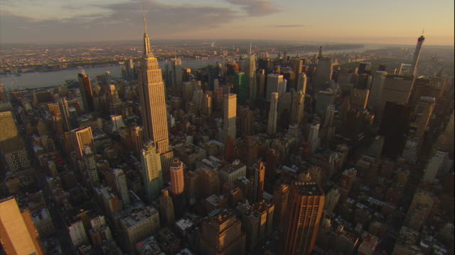 Aerial -Sunrise lights up the tall buildings of mid-town Manhattan, including the Empire State building, while flying toward Central Park.
