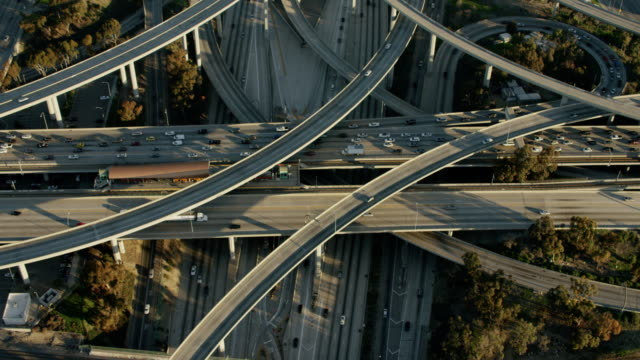 aerial sunrise view los angeles freeways and skyscrapers - autostrada interstatale americana video stock e b–roll