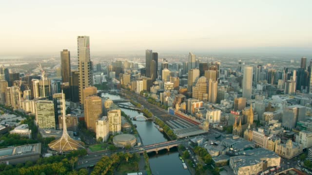 aerial sunrise view melbourne cbd along yarra river - spire stock videos & royalty-free footage