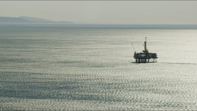 aerial sunrise view offshore oil rig california usa - industria petrolifera video stock e b–roll