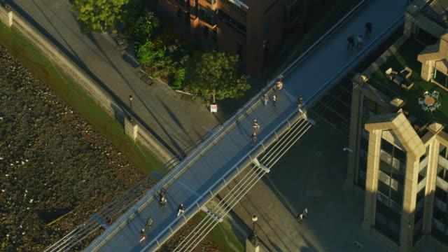 aerial sunrise view pedestrians crossing river thames london - london millennium footbridge stock videos and b-roll footage