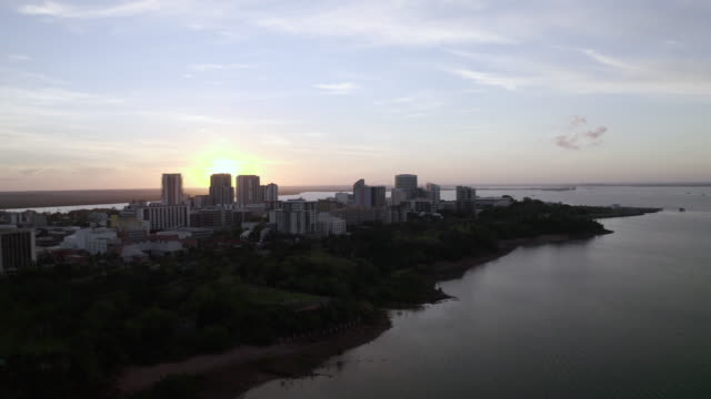 aerial: sunset behind buildings on a peninsula in front of the ocean in darwin - northern territory australia stock videos & royalty-free footage