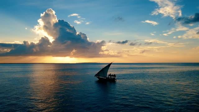 aerial/ sunset in paradise-flight over the ocean with dhow boat crossing, zanzibar island - タンザニア点の映像素材/bロール