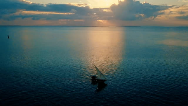 aerial/ sunset in paradise-flight over the ocean with dhow boat crossing, zanzibar island - ダウ船点の映像素材/bロール