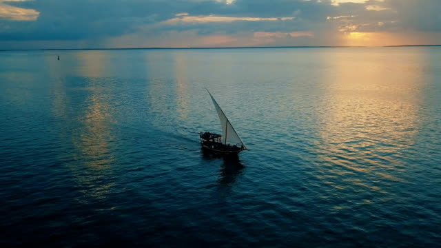 Aerial/ Sunset in paradise-flight over the ocean with dhow boat crossing, Zanzibar island