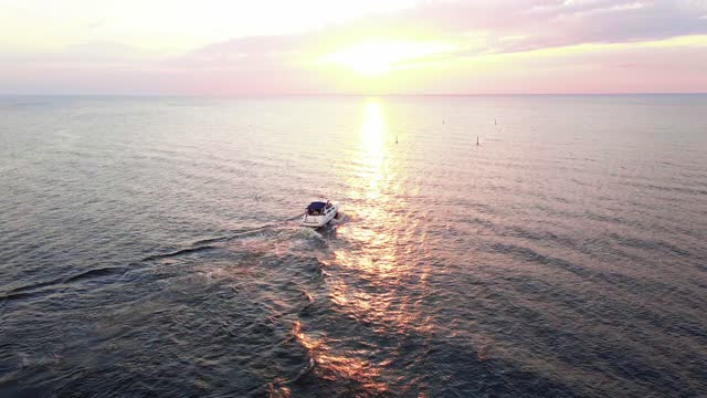 aerial sunset shot of yacht sailing during sunset with red and orange sky above reflecting sea - solstice stock videos & royalty-free footage