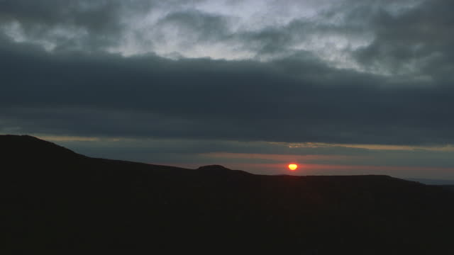 aerial sunset; slow zoom in (cloudy skies) with mountain tops in fg. - ireland stock videos & royalty-free footage