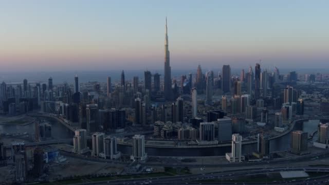 aerial sunset view burj khalifa dubai city skyscrapers - bay of water stock-videos und b-roll-filmmaterial