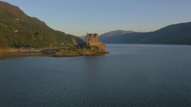 aerial sunset view eilean donan castle loch duich - see loch duich stock-videos und b-roll-filmmaterial