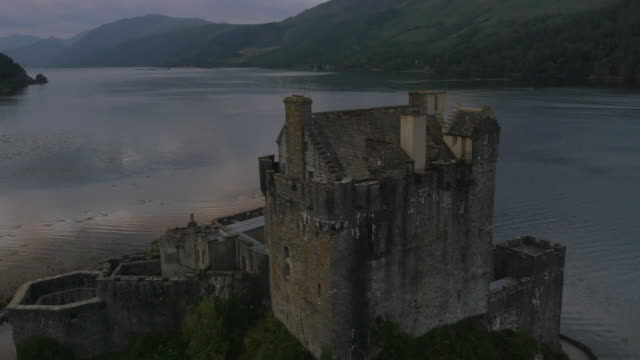 aerial sunset view eilean donan castle tourists scotland - scottish culture video stock e b–roll