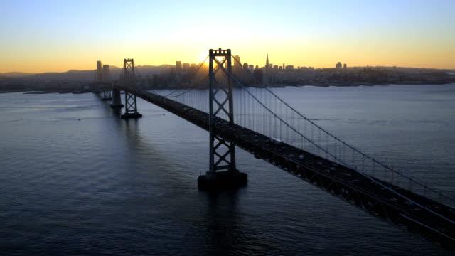 aerial sunset view oakland bay bridge san francisco - カリフォルニア州 サンフランシスコ点の映像素材/bロール