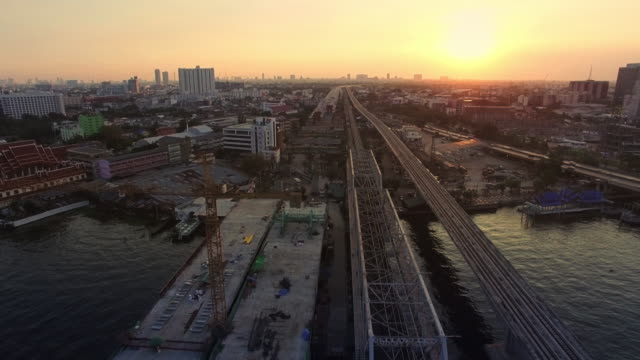 aerial sunset view shot of bridge construction site - bridge built structure stock videos and b-roll footage