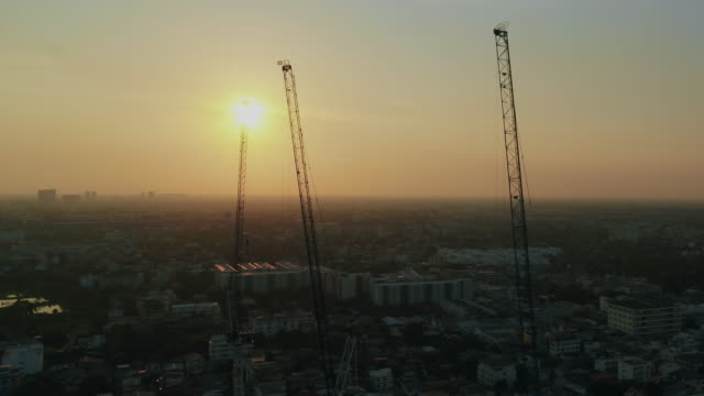 aerial sunset view shot of construction site silhouette - skyscraper stock videos & royalty-free footage