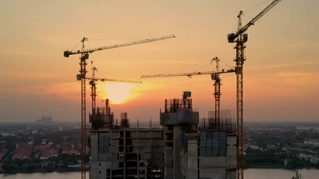 aerial sunset view shot of construction site - realizzazione video stock e b–roll