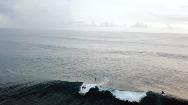 aerial: surfers catching a wave in bali sea in lombok, bali - fangen stock-videos und b-roll-filmmaterial
