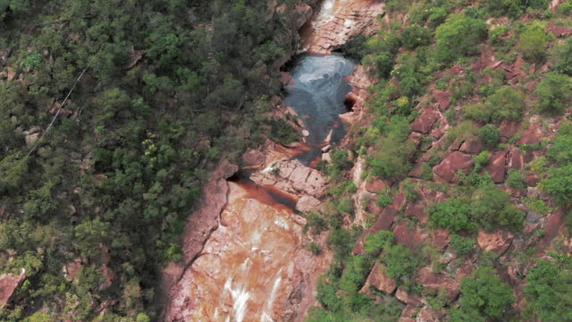 aerial: swift stream and scenic waterfall among lush green jungle in chapada, brazil - canyon stock videos & royalty-free footage