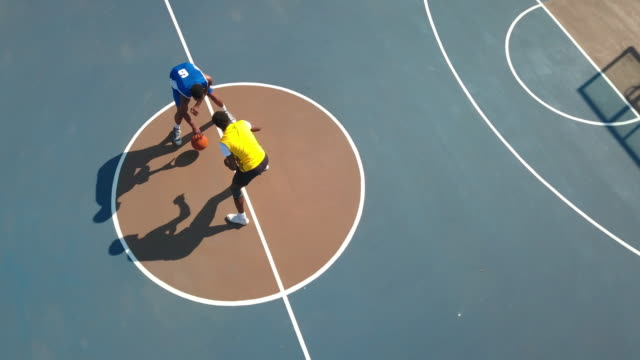 aerial swooping shot of expert basketball players dribbling in the middle of court - wettkampf stock-videos und b-roll-filmmaterial