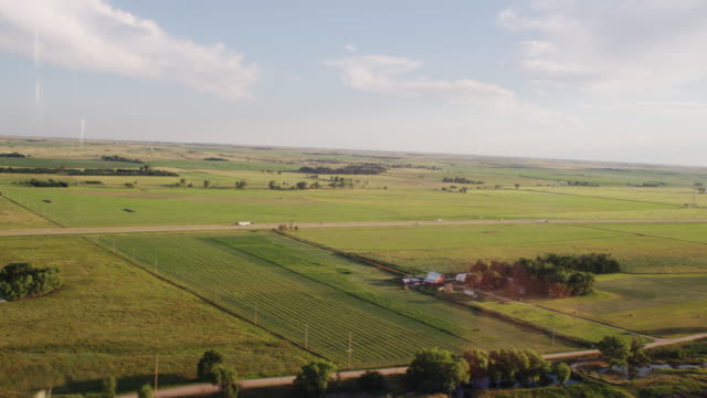 aerial tableau featuring green, flat plains; agricultural fields of crops, farm with red barn and semi trucks traveling an interstate highway under a blue sky with big white clouds. - nebraska stock videos & royalty-free footage