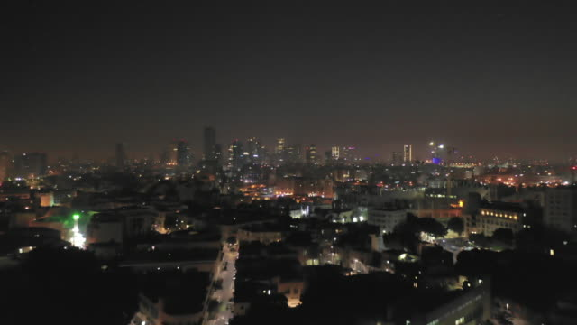 aerial: tel aviv at night with lit up skyline and illuminated streets - テルアビブ点の映像素材/bロール