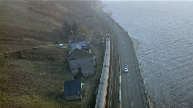 Aerial TGV train traveling along highway on coast / going through tunnel in hill / France