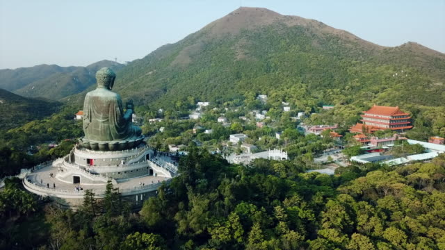aerial: the backside of tian tan buddha statue and a village in a forest - tian tan buddha stock videos and b-roll footage