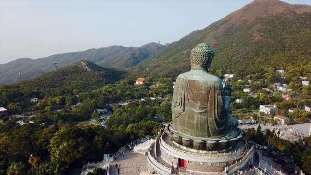aerial: the backside of tian tan buddha statue in a forest - tian tan buddha stock videos and b-roll footage