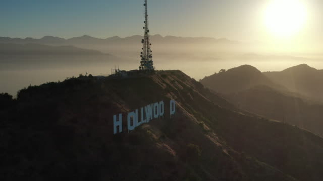 aerial: the hollywood sign and santa monica mountain range at sunset - hollywood, california - santa monica sign stock videos & royalty-free footage