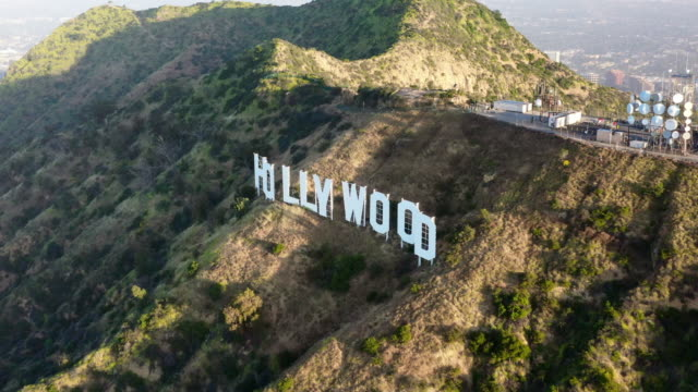 aerial: the hollywood sign on sunny day - hollywood, california - hollywood sign stock videos & royalty-free footage