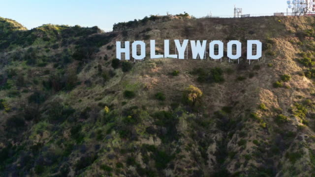 aerial: the hollywood sign on the side of mount lee on a beautiful sunny day - hollywood, california - hollywood sign stock videos & royalty-free footage