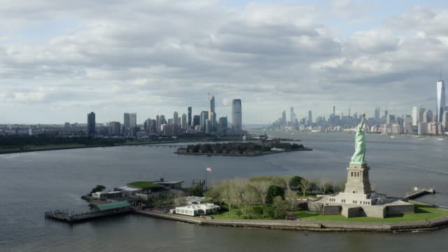 stockvideo's en b-roll-footage met aerial: the statue of liberty with new york city across the bay - new york city, new york - bovenste deel