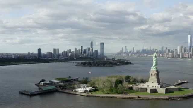 vídeos y material grabado en eventos de stock de aerial: the statue of liberty with new york city across the bay - new york city, new york - sección alta
