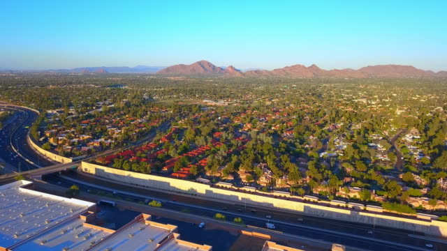 aerial: the sun shining on the homes and mountains - arizona stock-videos und b-roll-filmmaterial