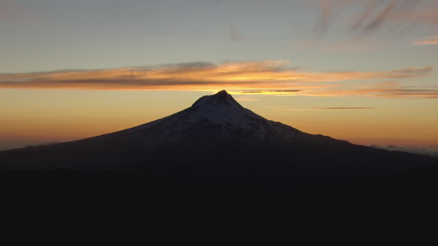 Aerial the sunrises behind a silhouetted Mt. Hood.