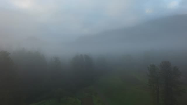 aerial: thick fog surrounding forest and mountains - thick stock videos & royalty-free footage