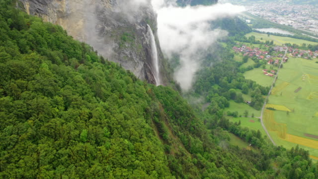 aerial: thin waterfall among lush green on stunning mountain over picturesque town - chamonix, france - lush video stock e b–roll