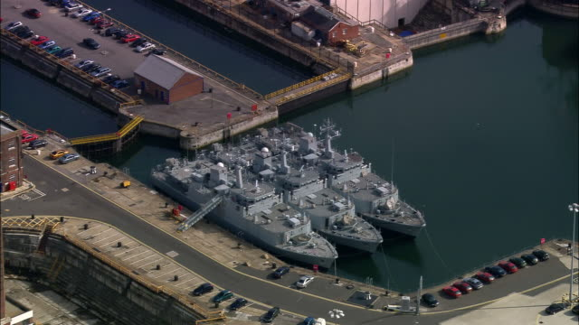 Aerial three ships docked at naval base/ Portsmouth, England