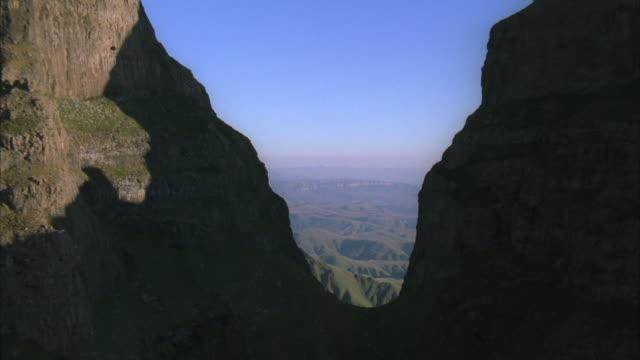 aerial through a gap of two peaks to reveal a breathtaking mountainous landscape - drakensberg mountain range stock videos & royalty-free footage