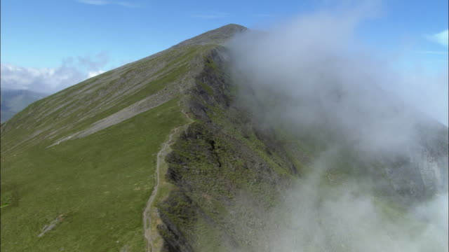 aerial through cloud and past mountain peak in snowdonia, wales, uk - スノードニア点の映像素材/bロール
