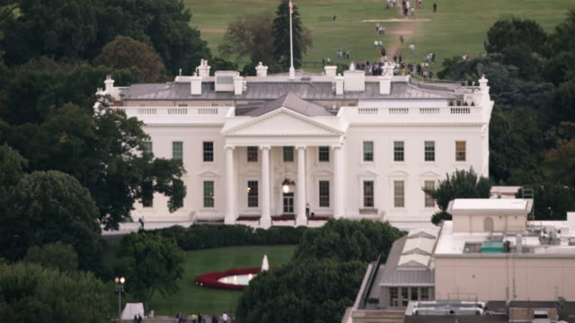 vídeos de stock e filmes b-roll de aerial tight shot of the white house surrounded by trees, dc daytime - washington dc