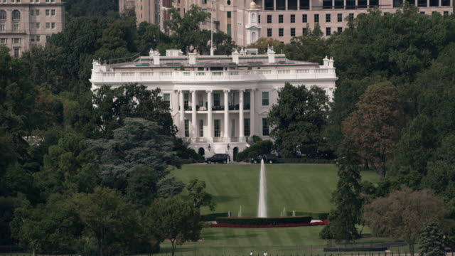 aerial tight shot of the white house surrounded by trees, dc daytime - weißes haus stock-videos und b-roll-filmmaterial