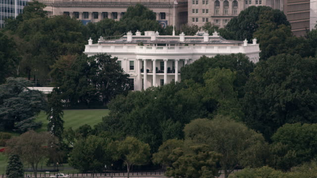 aerial tight shot of the white house surrounded by trees then camera zooms out, dc daytime - la casa bianca washington dc video stock e b–roll