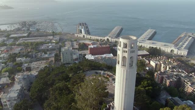 aerial tilt down moving past coit tower on telegraph hill to pioneer park on a cheerful sunny day with the bay and famous piers in the background - san francisco, california - coit tower stock videos & royalty-free footage