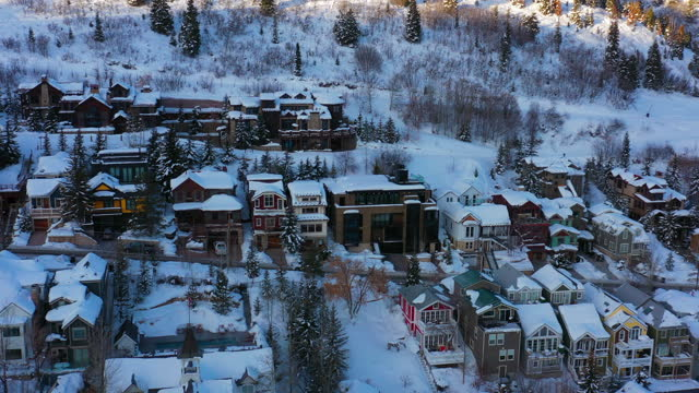 aerial tilt down over a quaint snow-covered town nestled in the mountains with evergreen trees and quiet neighborhood streets - park city, utah - park city stock videos & royalty-free footage