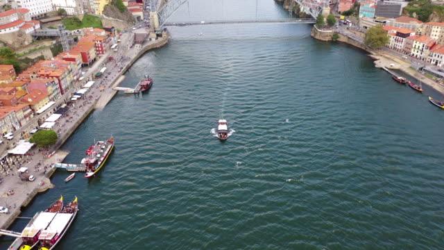 vídeos de stock e filmes b-roll de aerial tilt down shot of boat in river against famous bridge, drone flying over nautical vessels amidst buildings in city - porto, portugal - ponte
