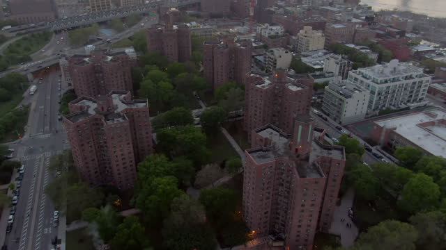 aerial tilt down shot of bridges on east river amidst buildings in city at sunset, drone flying forward towards manhattan against sky - new york city, new york - tilt stock videos & royalty-free footage