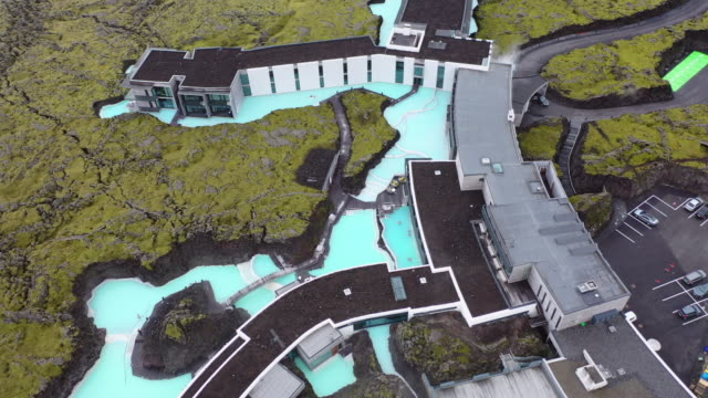 aerial tilt down shot of buildings on geothermal spa and rock formation, drone flying over famous natural lagoon - blue lagoon, iceland - iceland stock videos & royalty-free footage