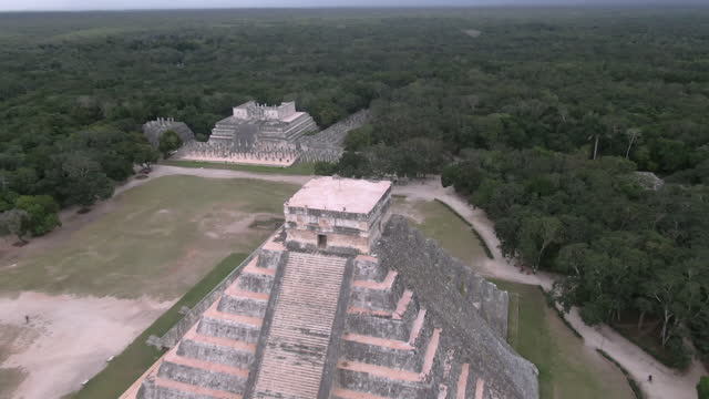 aerial tilt down shot of chichen itza amidst trees against cloudy sky, drone flying forward towards famous historic landmark - tilt down stock videos & royalty-free footage